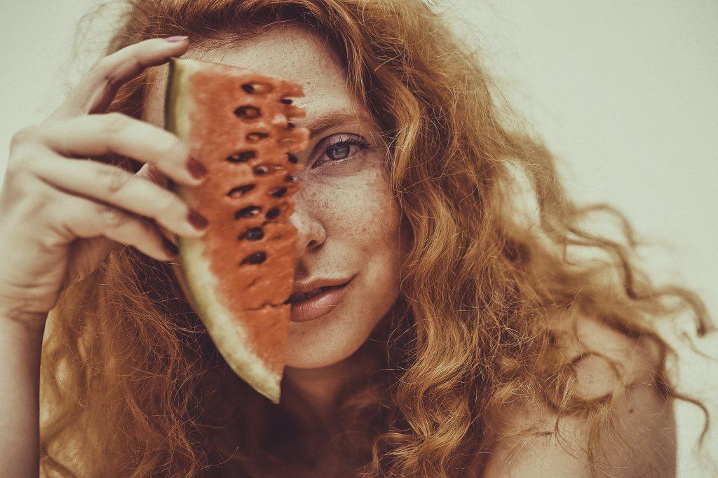Frau mit roten Haaren und Melone im Gesicht